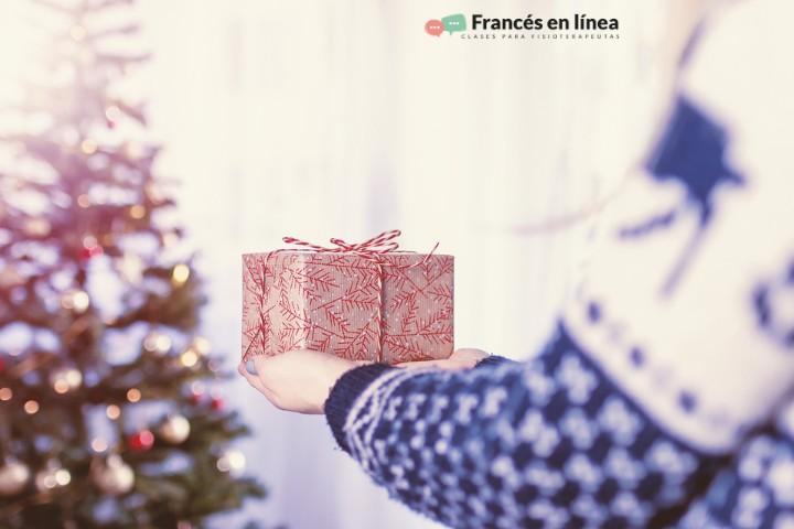 Una persona entraga un regalo de Navidad. En el fondo se ve el árbol de Navidad